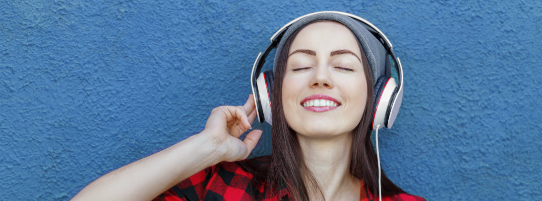girl in a red plaid shirt listening to music on her headphones