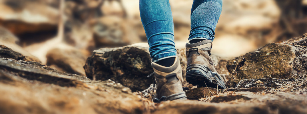 person in jeans and boots hiking over rocky terrain