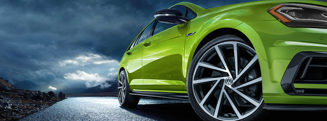 2019 Volkswagen Golf R exterior shot with viper green color paint job low angle shot of turning wheel and a dark cloudy sky