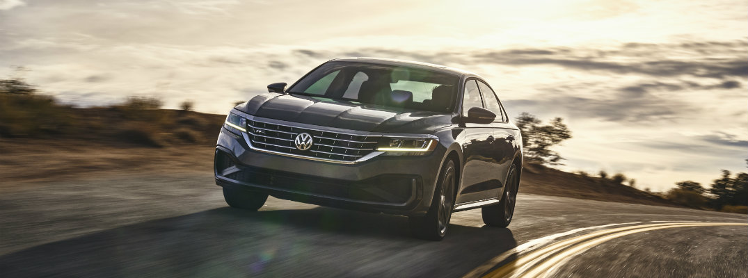 2020 Volkswagen Passat exterior shot with silver gray paint color driving on a curving mountain road with a bright cloudy sky behind it