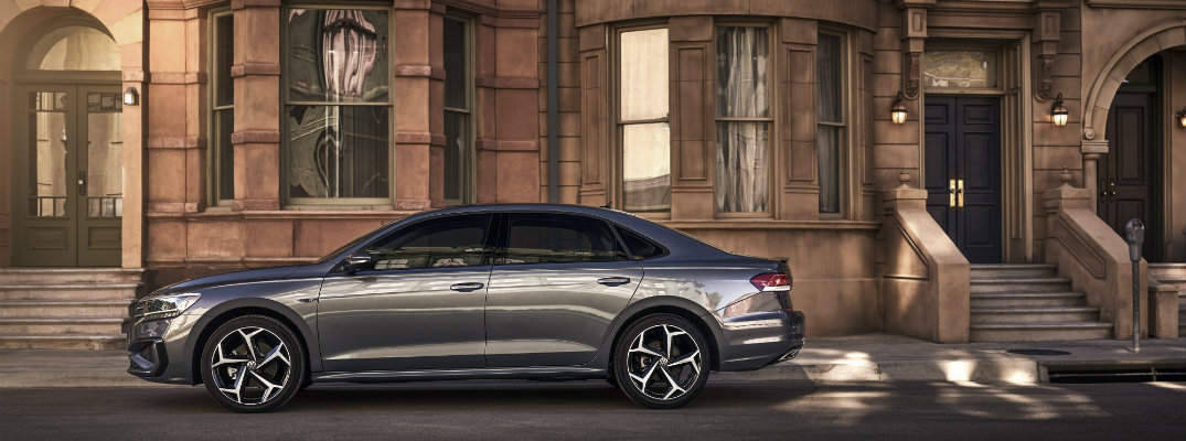 2020 Volkswagen Passat exterior side shot with dark gray metallic paint color parked outside an old fashioned brick and stone apartment building