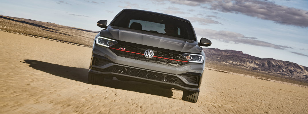 2019 Volkswagen Jetta GLI exterior front shot angled and showcasing red stripe on grille and GLI tag as it drives through a desert