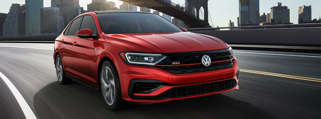 2019 Volkswagen Jetta GLI exterior shot with Tornado Red paint color driving under a bridge just outside a city skyline