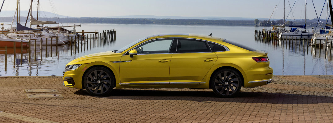2019 Volkswagen Arteon R-Line exterior side shot with tumeric yellow paint color parked near a pier dock lined with boats at sea