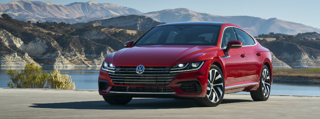 2019 Volkswagen Arteon SEL Premium R-Line exterior shot with chili red metallic paint color parked outside next to a lake and a mountain range