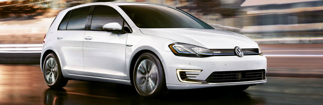2019 Volkswagen e-Golf exterior side shot with pure white paint color driving with a blurred orange background