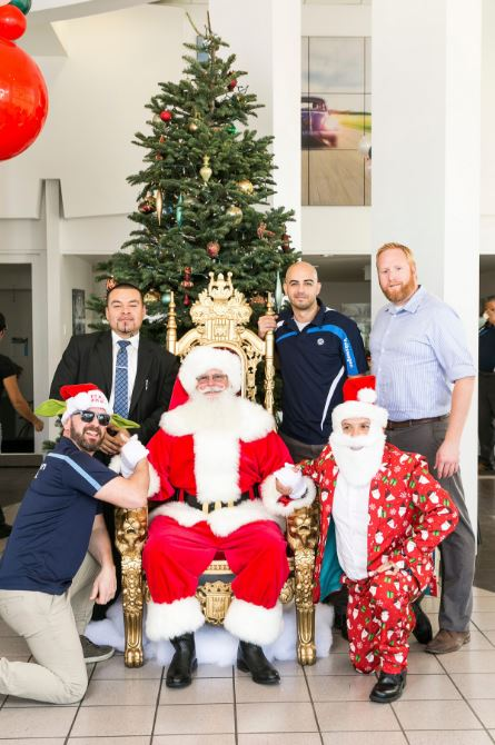 Five Men Posing for a Photo with Santa
