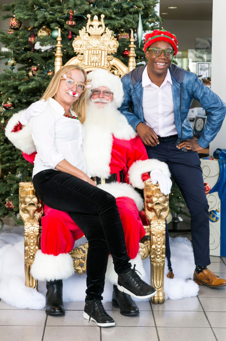 Woman Sitting on Santa's Lap and Man Sitting on the Edge of Santa's Chair