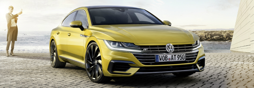 Woman Taking a Photo of a Yellow 2019 Volkswagen Arteon