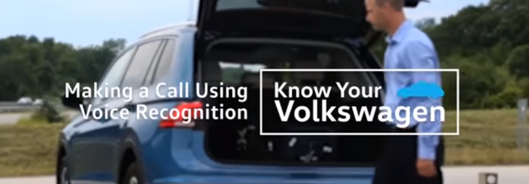 Making a Call Using the Voice Recognition Title and a man standing near the cargo area of a blue Volkswagen Tiguan