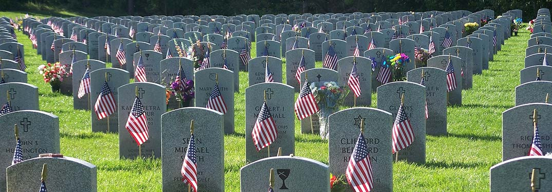 A military cemetery with many gravestones and American flags