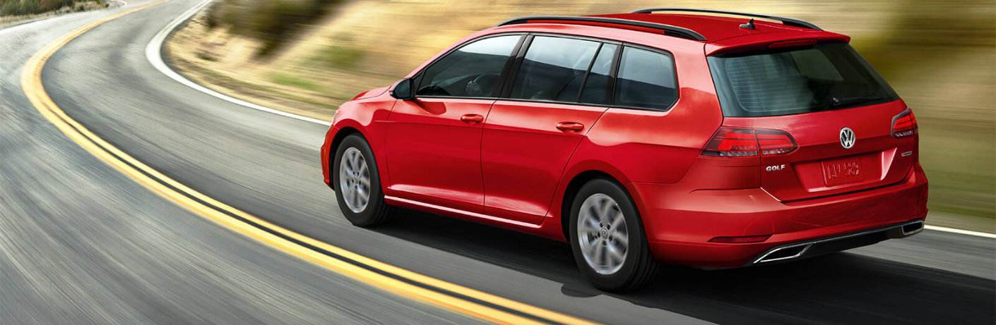 Red 2019 Volkswagen Golf SportWagen driving on a curvy road