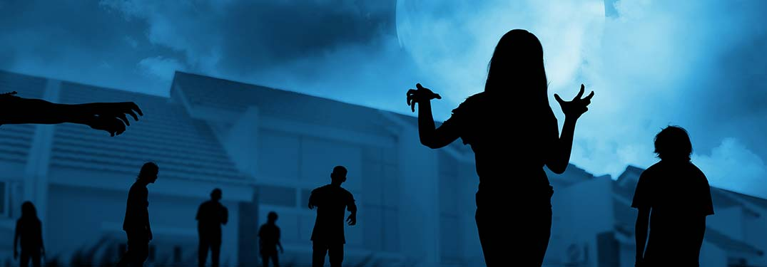 Silhouettes of zombies walking in front of a house at night
