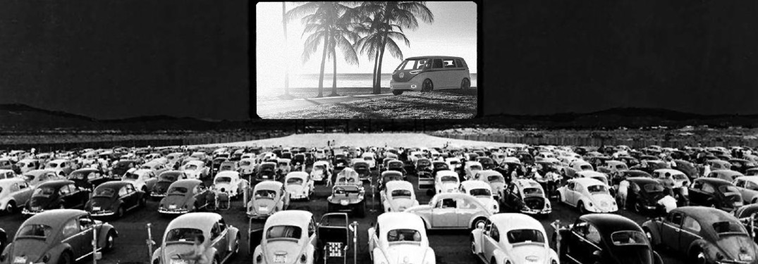 Classic Volkswagen Beetle models at a drive-in movie theater with a VW ID Buzz on the movie screen