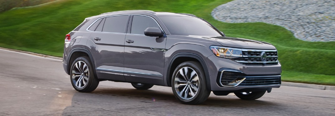 Grey 2020 Volkswagen Atlas Cross Sport driving by a grassy hill