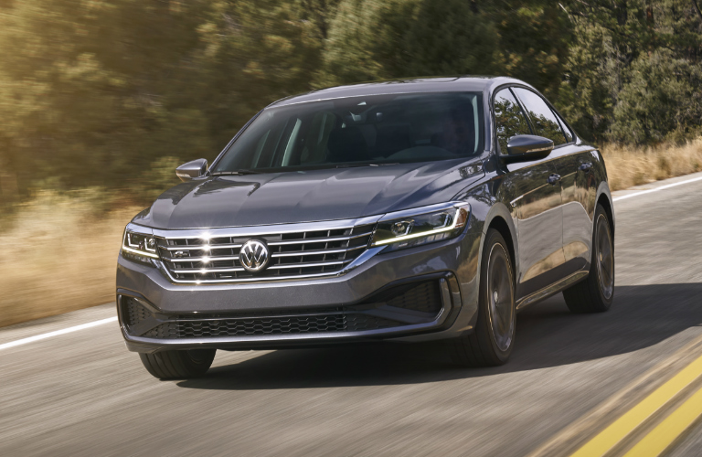Front view of grey 2020 Volkswagen Passat driving by a forest