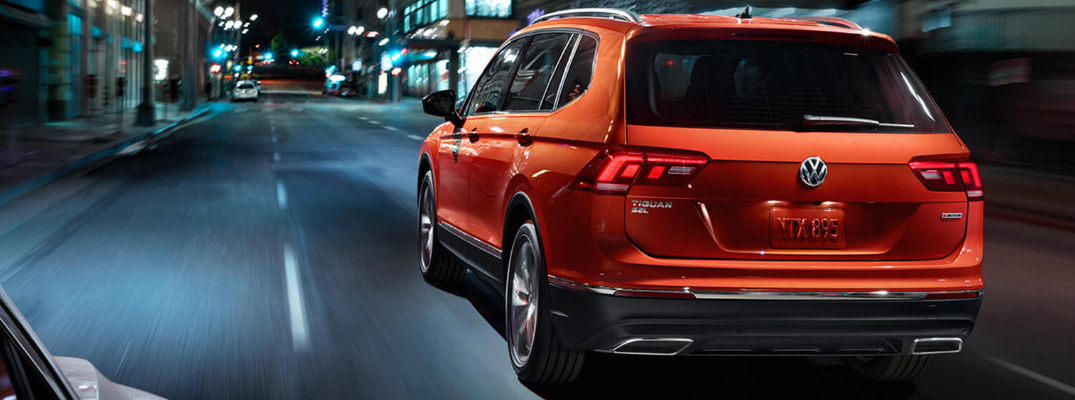 Orange 2019 Volkswagen Tiguan driving at night on a city street