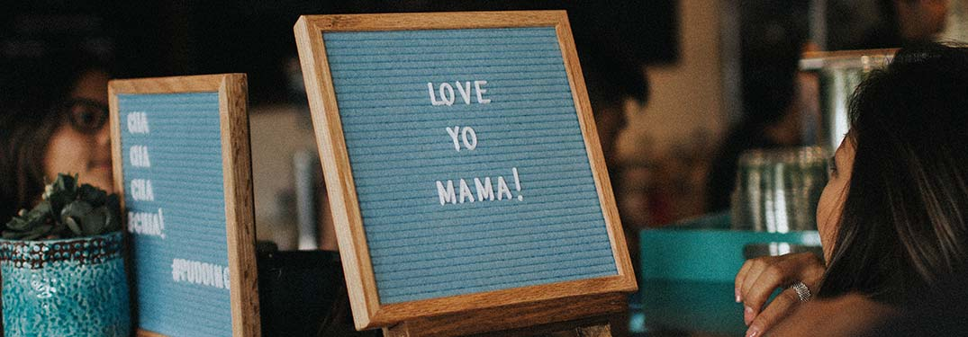 "A woman looking at a ""Love Yo Mama!"" sign"