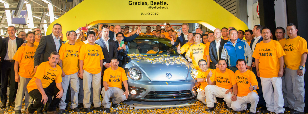 Production workers at Volkswagen de Mexico's Puebla plant standing next to the last production VW Beetle