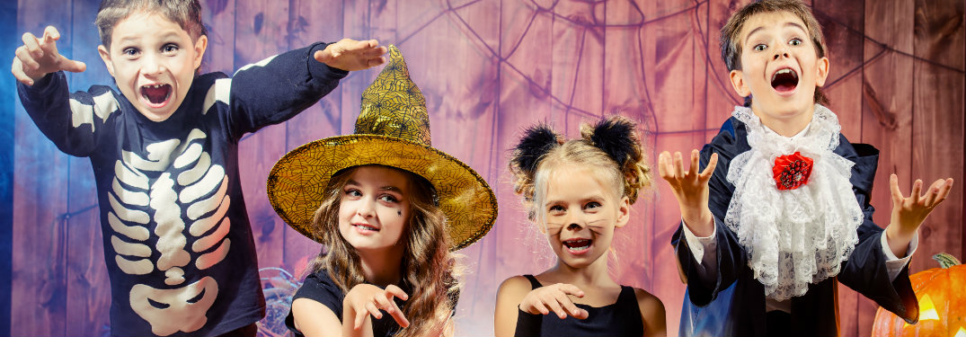 Children in Halloween costumes striking scary poses