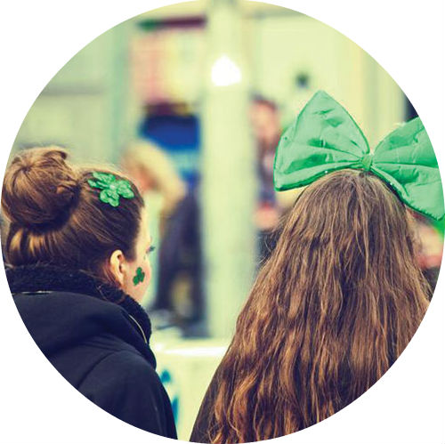 two girls wearing green bows watching St. Patrick's Day parade
