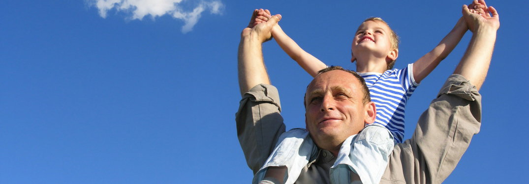 little boy on dads shoulders outside