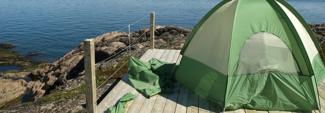 camping tent set up in front of water