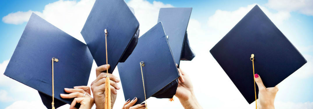 Hands throwing up hats after graduating