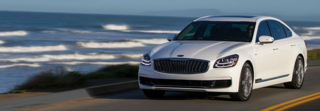 2019 Kia K900 in White Coloring Driving Down Road