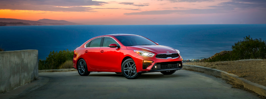 2019 Kia Forte parked by stone wall at sunset