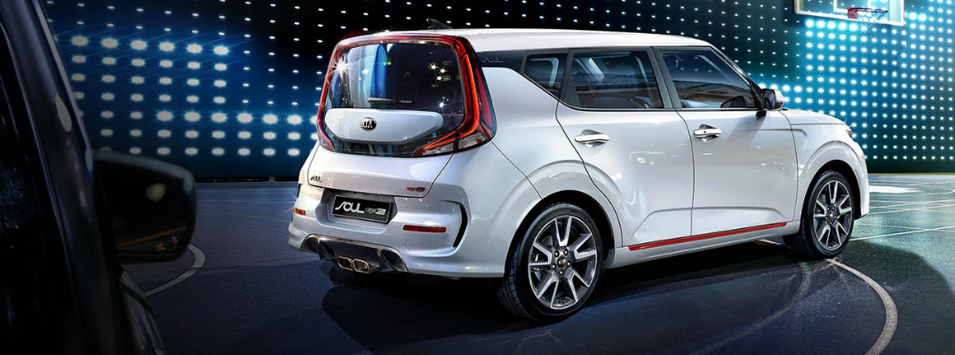 2020 Kia Soul exterior rear shot with white paint color showcasing new trunk, bumper, and taillight design while parked on a lit up basketball court