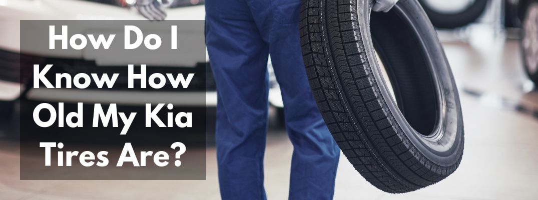 "Mechanic carrying a tire with ""How Do I Know How Old My Kia Tires Are?"" white text"