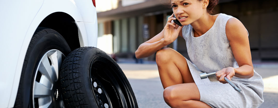 How to Change a Tire on Your Volkswagen Passat at Karen Radley Volkswagen-Woodbridge VA-Woman Trying to Change a Flat Tire