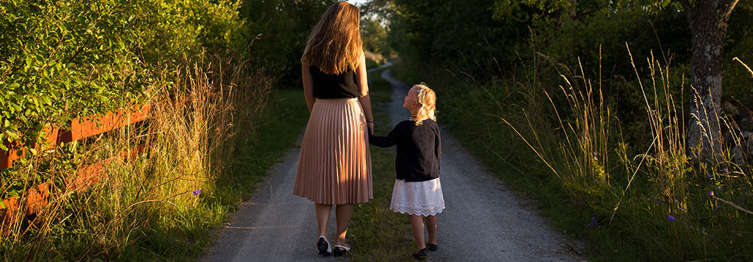 Mother and daughter holding hands and walking down a trail