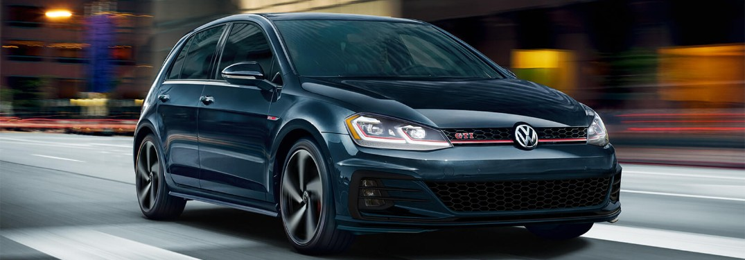 Front passenger angle of a blue 2019 Volkswagen Golf GTI driving down a road