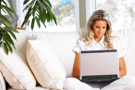 Woman sitting on her couch while using her laptop