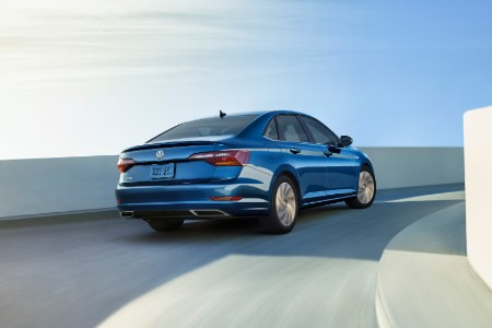 Rear passenger angle of a blue 2019 Volkswagen Jetta driving down a road