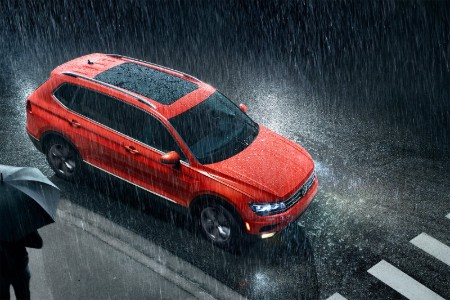 Front passenger aerial angle of an orange 2019 Volkswagen Tiguan driving in the rain