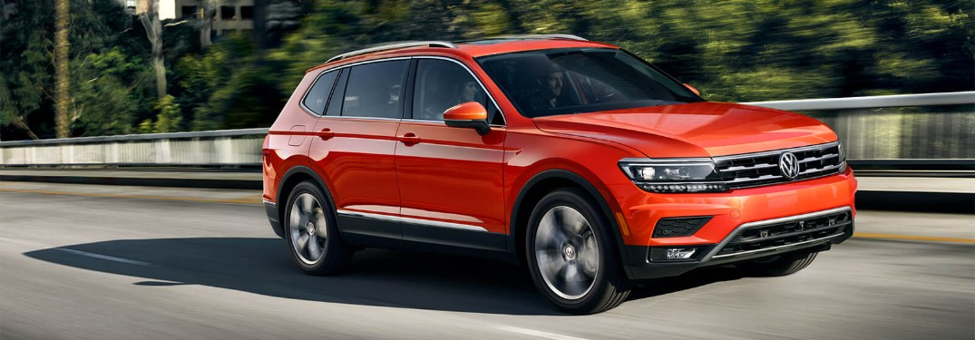Front passenger angle of an orange 2019 Volkswagen Tiguan driving down a road