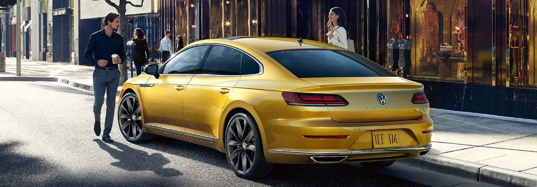 Rear driver angle of a yellow 2019 Volkswagen Arteon with a man by the driver door and a woman on the passenger side
