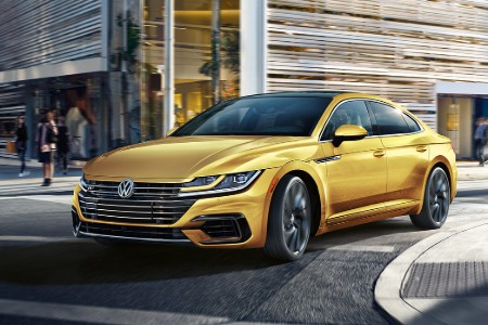 Front driver angle of a yellow 2019 Volkswagen Arteon driving on a curvy city street