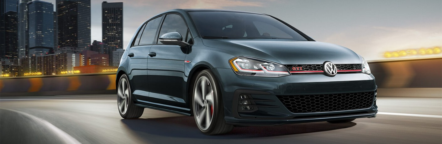 Front passenger angle of a blue 2019 Volkswagen Golf GTI driving away from a city