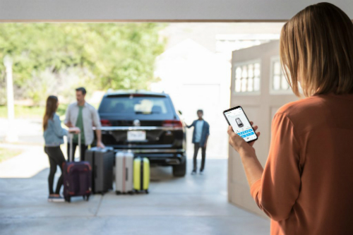 Woman using CarNet app to get VW vehicle ready for a trip.