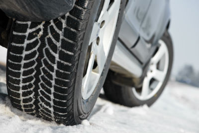 Car with winter tires parked on snow surface