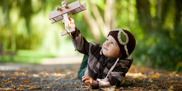 Kid with Toy Airplane Playing on the Ground