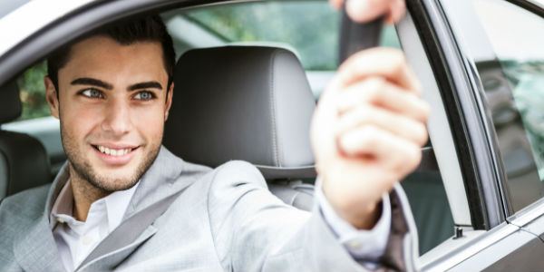 Man Holding Key Fob and Sitting In Car