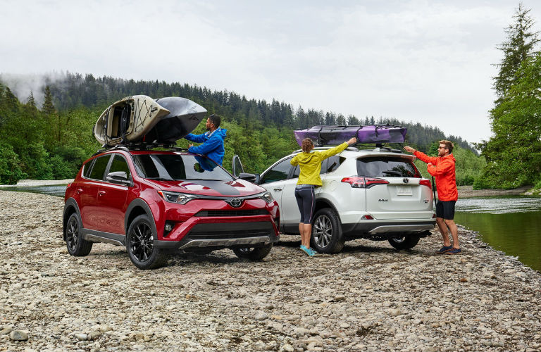Two 2018 Toyota RAV4 models with kayaks strapped to the top parked near a lake