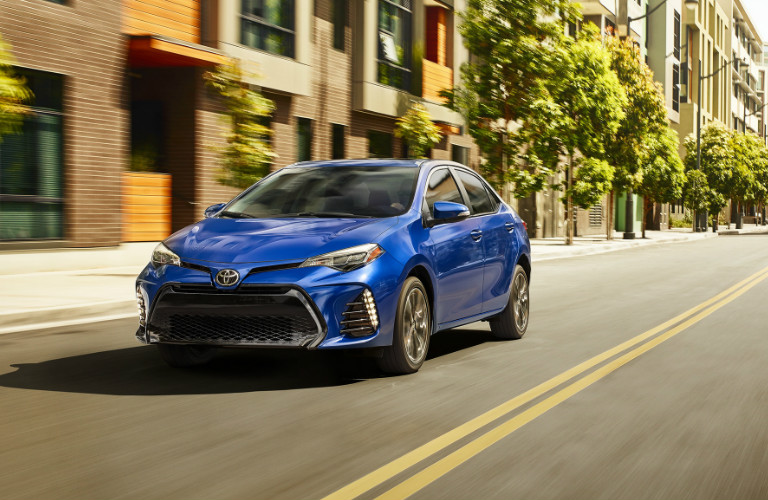 2019 Toyota Corolla In Blue Driving Down A Deserted City Street O