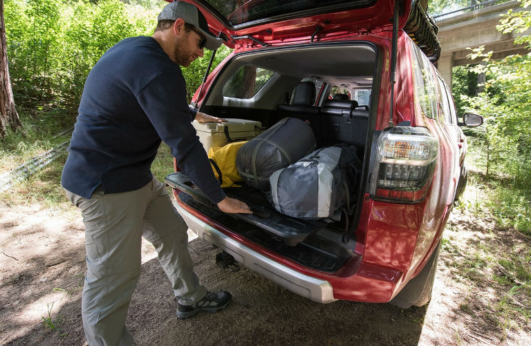 Man pulling out the rear cargo deck on the 2018 Toyota 4Runner