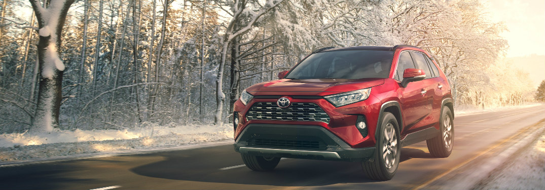 Toyota RAV4 in red driving down an empty road in winter